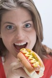 Woman eating a hot dog with mustard