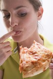 Young woman with partly eaten slice of pizza licking her finger