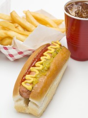 A hot dog, a portion of chips and a plastic cup of cola