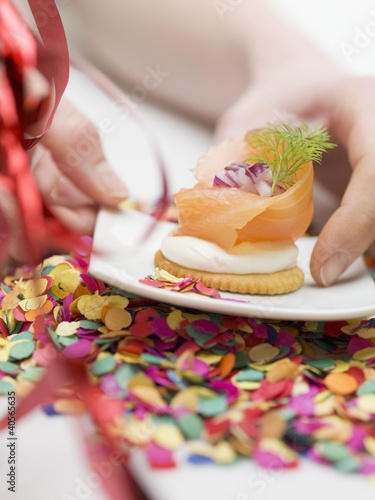 Hand reaching for cracker topped with smoked salmon