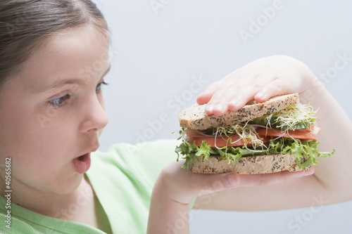 Girl looking at a large sandwich