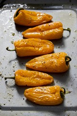 Six yellow peppers on a baking tray