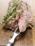Roast saddle of venison with rosemary, piece on meat fork