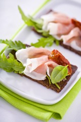 Raw ham, rocket and dried tomatoes on wholemeal bread