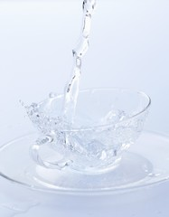Pouring water into a glass cup