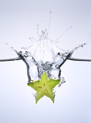 Slice of carambola falling into water