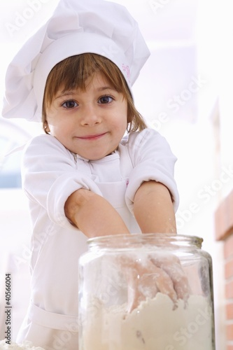 Little girl taking flour out of jar with both hands