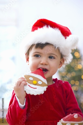 Little girl in Santa hat eating a biscuit