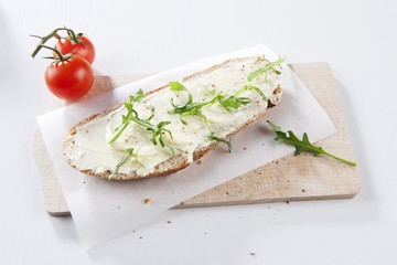 Bread and butter with rocket on a board