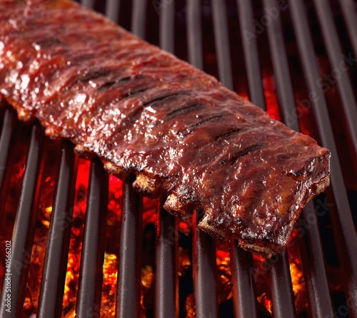 Whole Rack of Pork Ribs on Grill with Barbecue Sauce