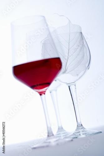 Glass of red wine and empty wine glasses