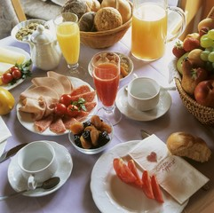 Breakfast table with juices, cold cuts and fruit