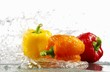 Peppers (yellow, orange, red) with splashing water