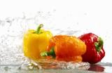 Peppers (yellow, orange, red) with splashing water