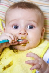 Baby eating baby food from spoon