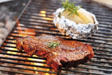 T-bone steak and baked potato on barbecue rack