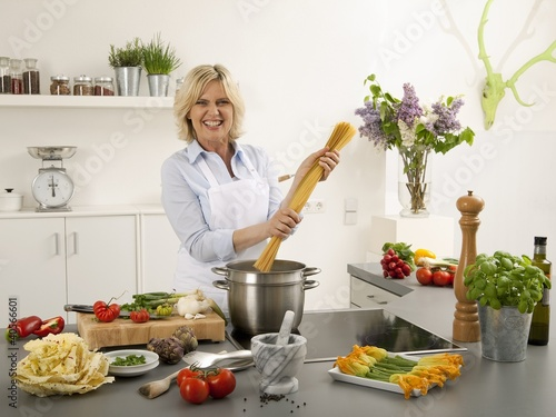 Woman laughing with spaghetti in her hands