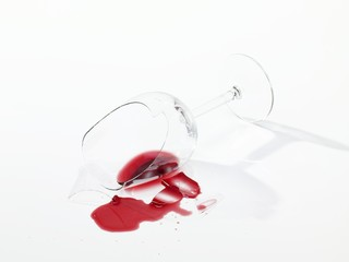 Broken wine glass with spilt red wine