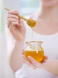 Young woman holding jar of honey and honey dipper