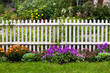 White picket fence surrounded by garden flowers in yard