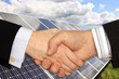 Businessmen shaking hands in front of Solar Power Station