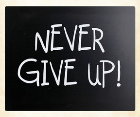 """""""Never give up"""" handwritten with white chalk on a blackboard"""