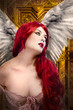Beautiful gothic sexy angel with wings, red hair over gold backg
