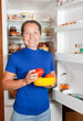 woman taking tomato of the fridge