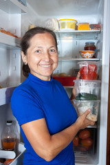 woman putting   vegetables  into refrigerator