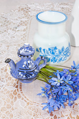 bluebel, vase and teapot on a lace tablecloth, still life