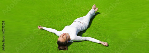 Full-length beautiful woman on the grass in white clothes