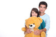 Teenage couple with a large stuffed bear