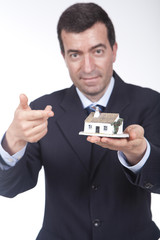 businessman with a small house in his hand