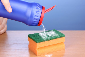 Sponge with scouring powder on wooden table on blue background