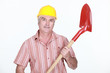 mature bricklayer holding shovel against studio background