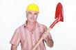 mature bricklayer holding shovel against studio background