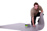 Man putting down linoleum flooring
