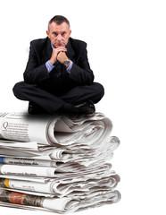 uomo d'affari seduto sopra dei giornali