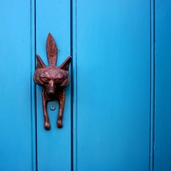 Blue door with an ornate fox face door knocker