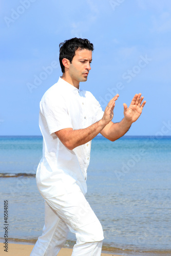Handsome man on the beach meditating