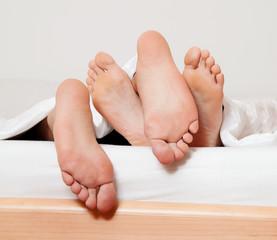 Füße eines Paares im Bett.