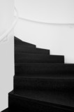 Spiral staircases between white walls and black floor