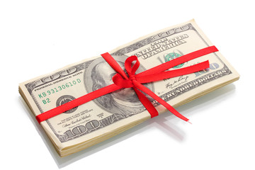 A lot of one hundred dollar bills tied red ribbon isolated