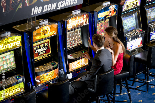 Young couple playing with slot machines