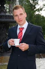 Young man in suit with a cup