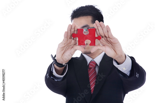 Businessman showing a piece of puzzle