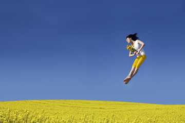 Happy Woman jumping with flower