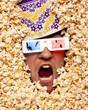 Surprised face in popcorn watching 3D movie