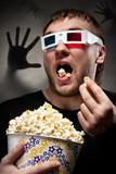 Scared man watching 3D movie