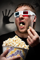 Scared man watching 3D movie